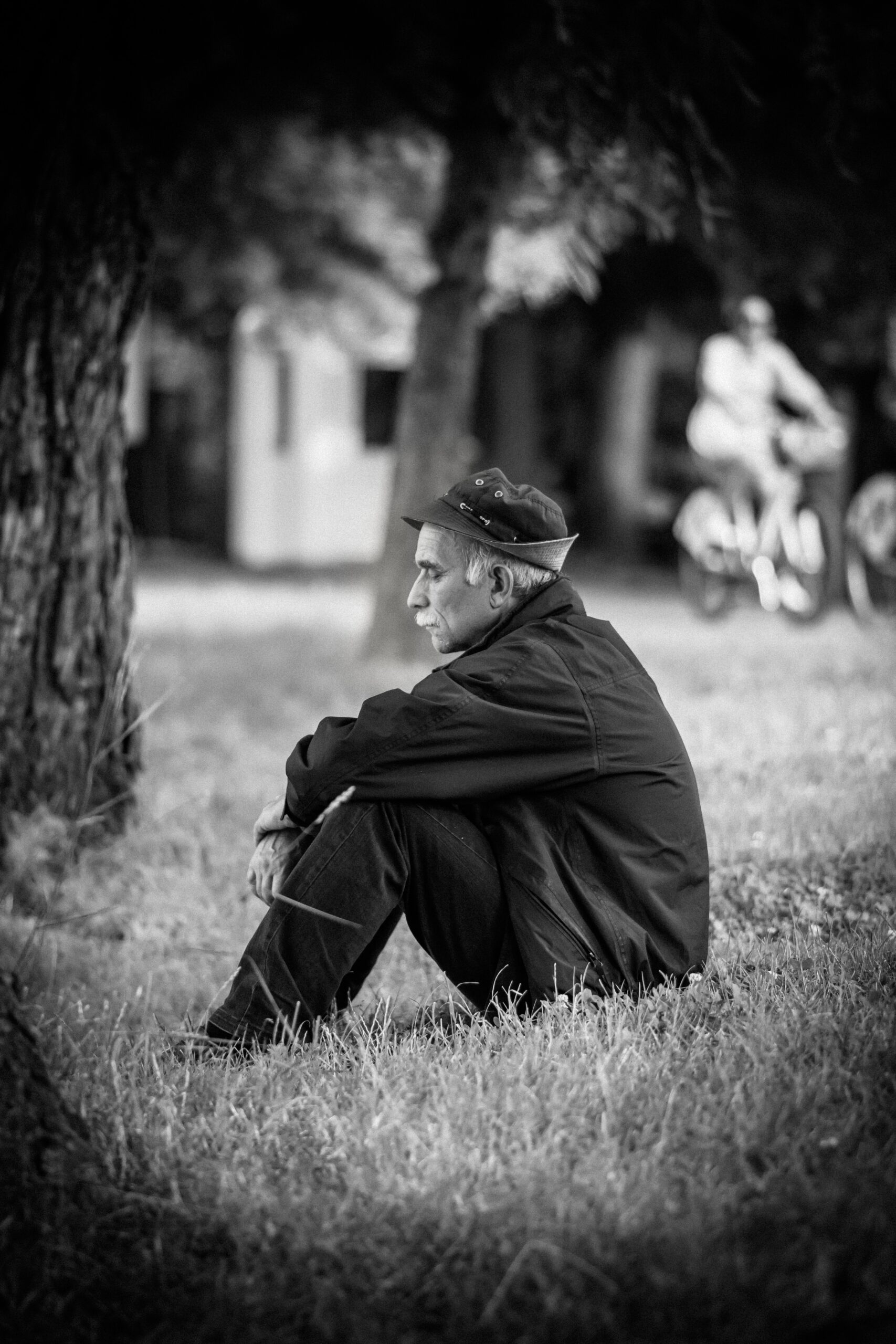 Black and white photo of an older man sitting on the grass near a tree.