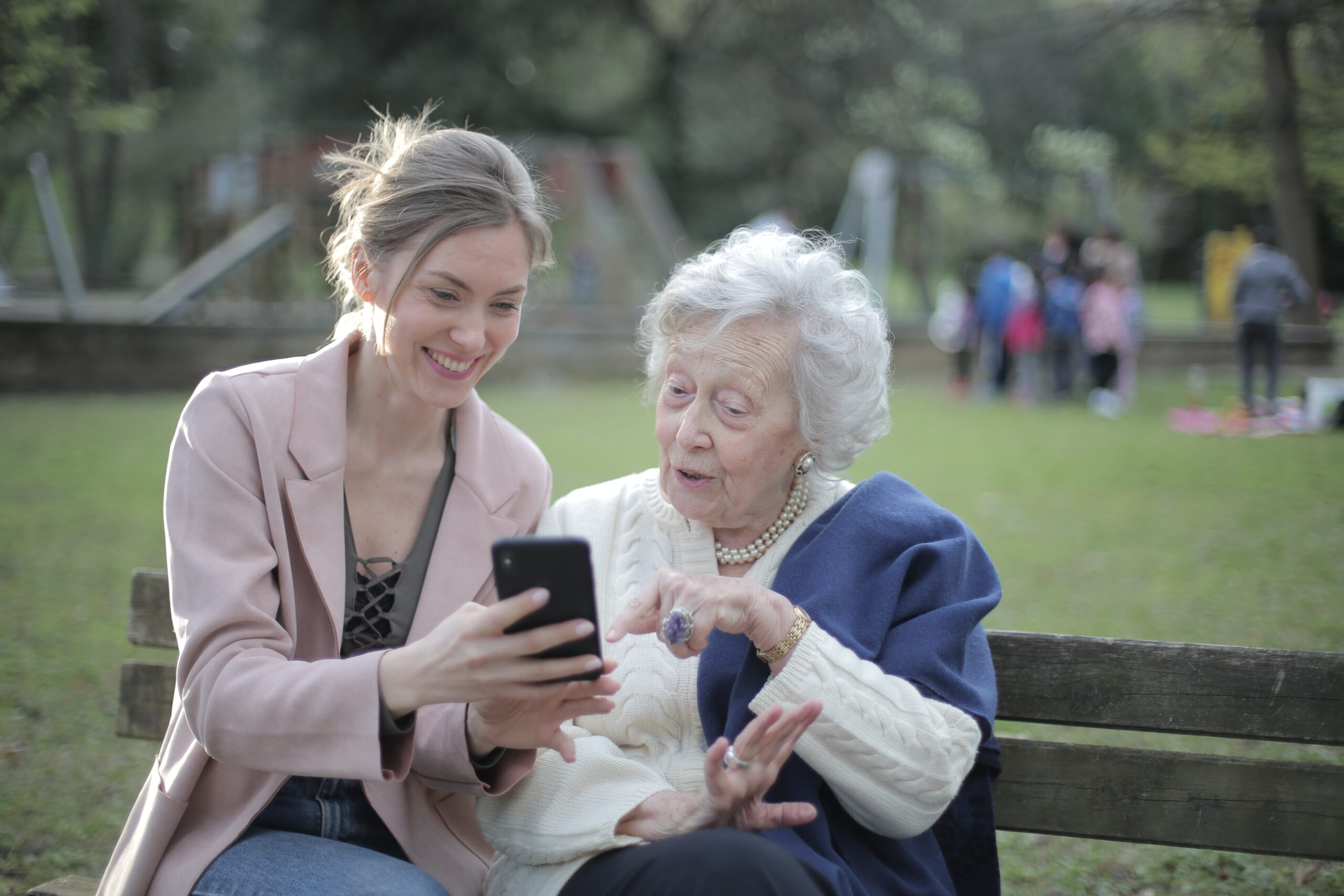 Adult daughter sitting on a park bench with her senior mother showing images on a smartphone