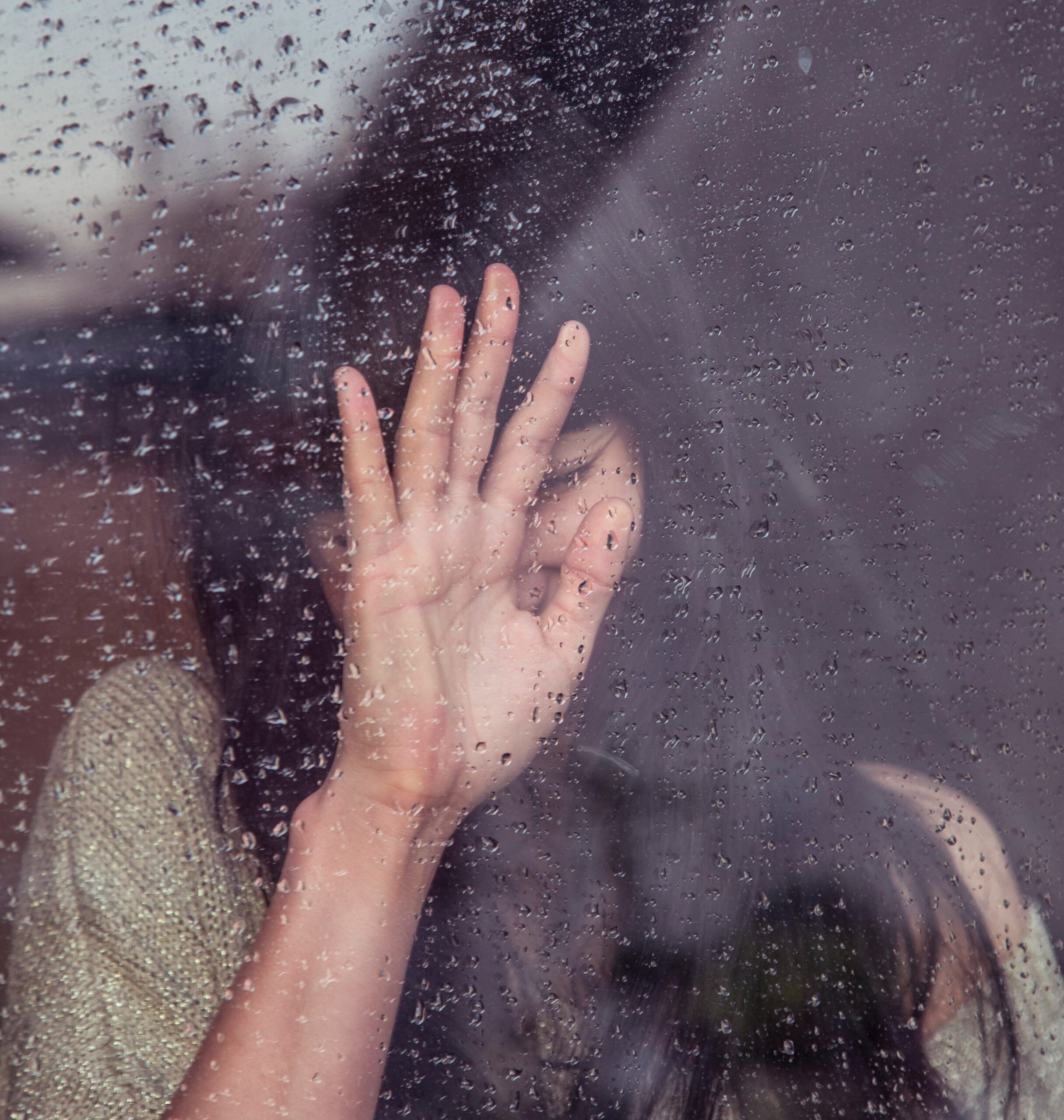 Young lady crying with her hand on window covered with raindrops