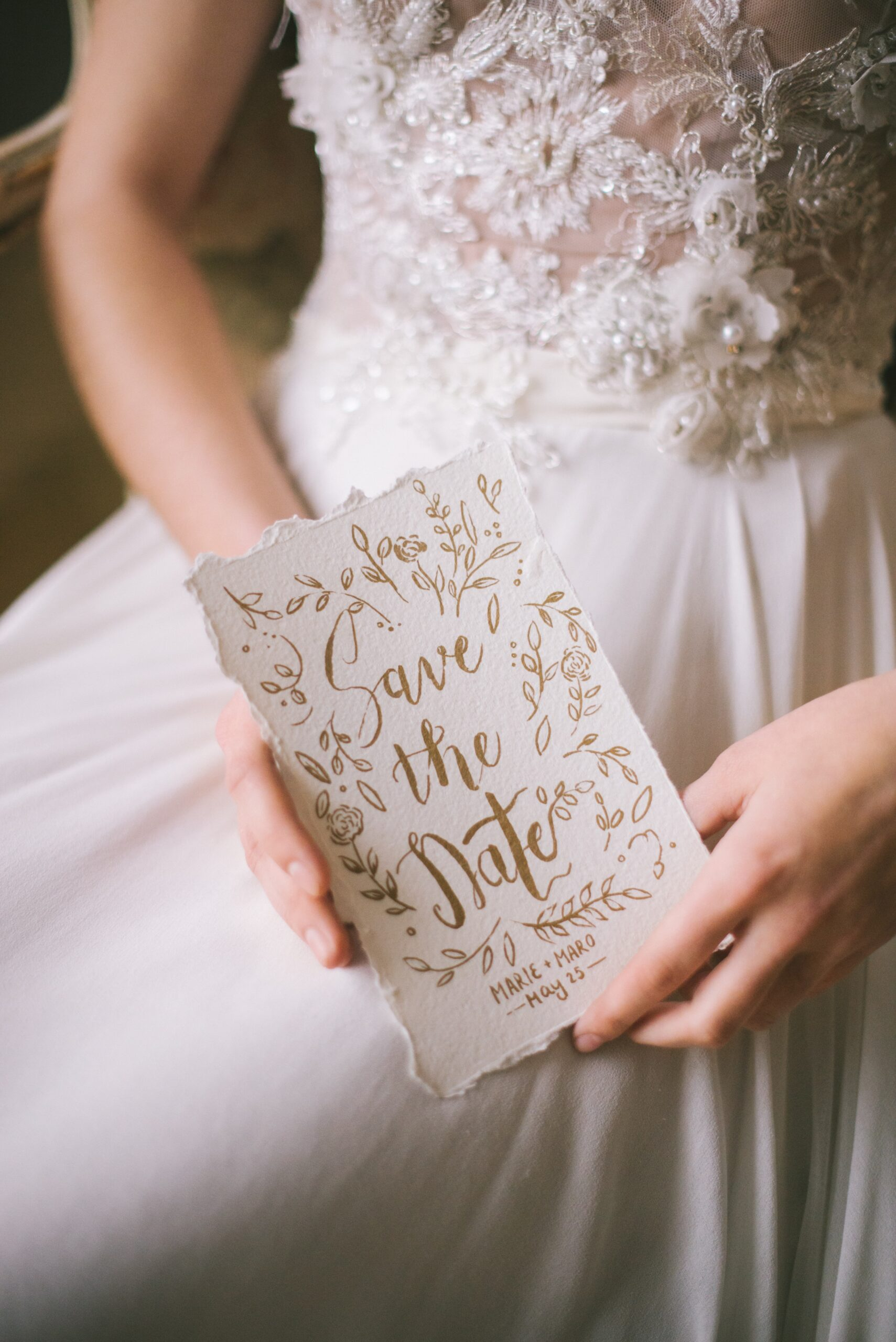 """Bride holding a white invitation with gold lettering and the words """"Save the Date"""" on the front"""