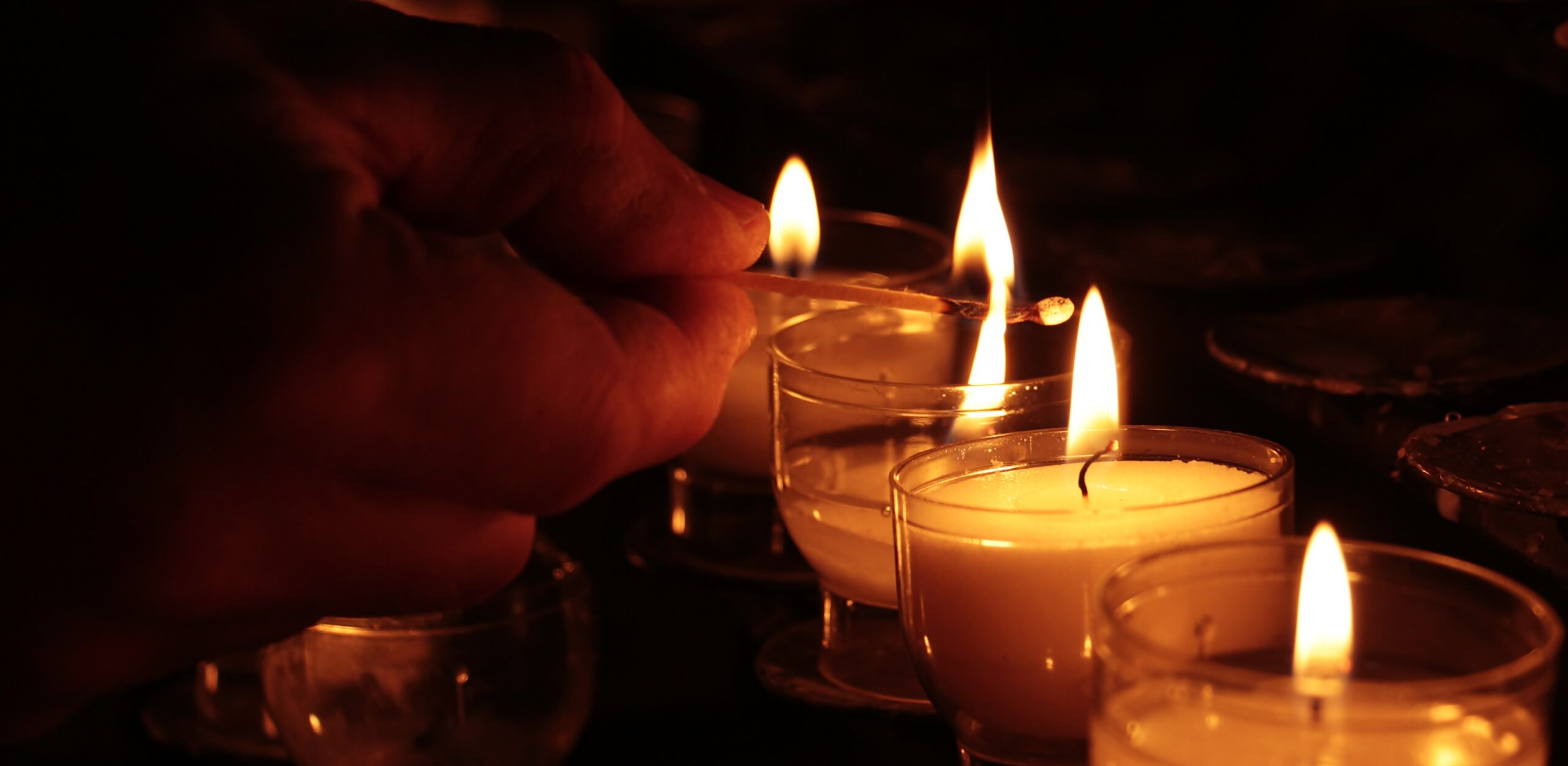 Hand holding a lit match and lighting 3 tealight candles